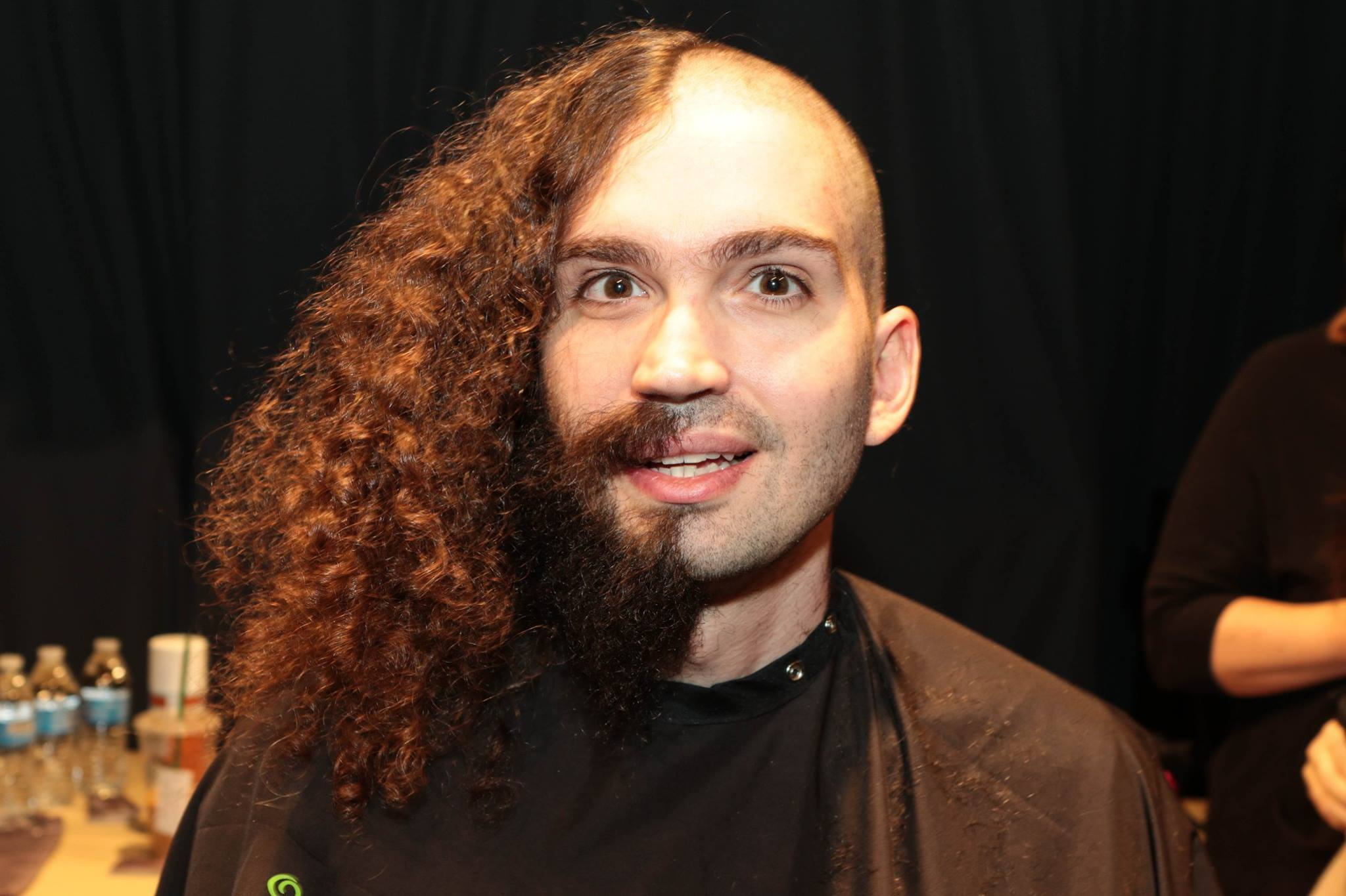 Man with hair and beard half shaved off