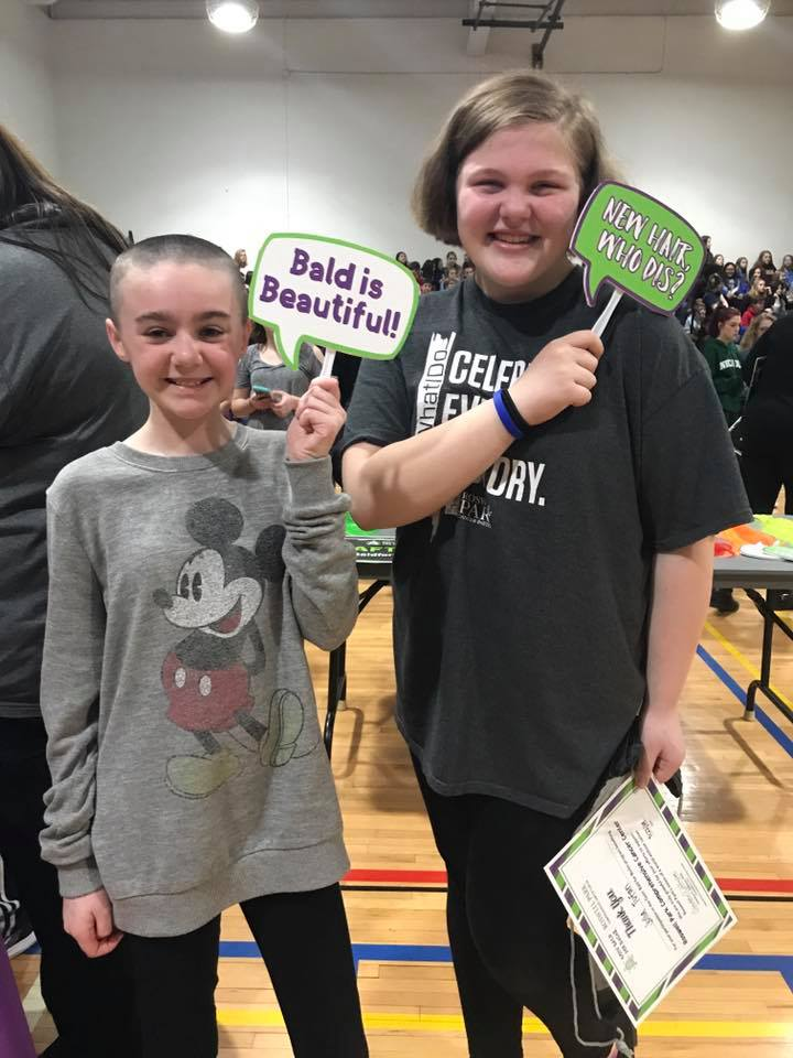 """Two children holding Bald for Bucks signs that say """"New hair, who dis?"""" and """"Bald is beautiful"""""""