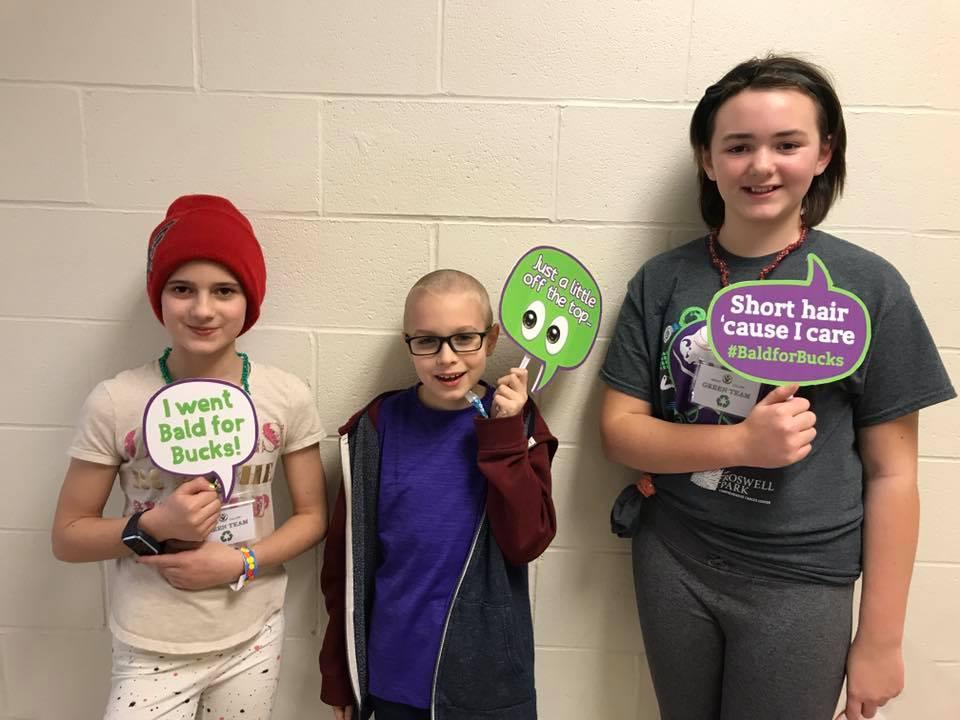 3 children holding Bald for Bucks signs up