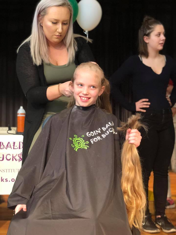 Adult shaving child's hair as she smiles and holds up hair that was cut off
