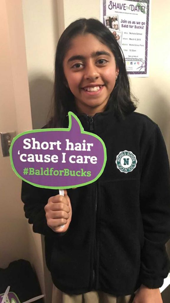 """Person with """"Short hair 'cause I care"""" Bald for Bucks sign"""