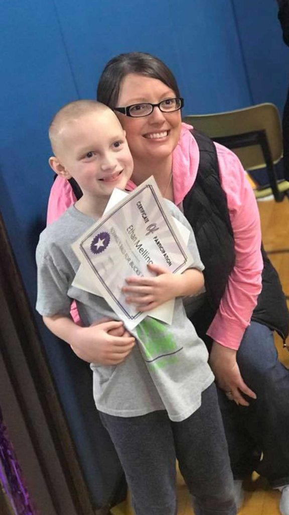 Adult hugging child with shaved head and Bald for Bucks certificate