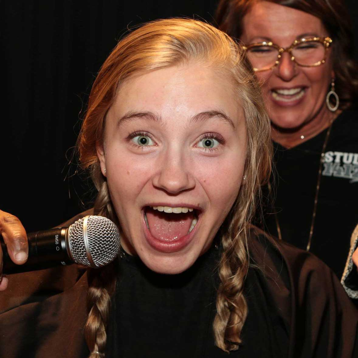 Excited girl with microphone and Bald for Bucks volunteer in background
