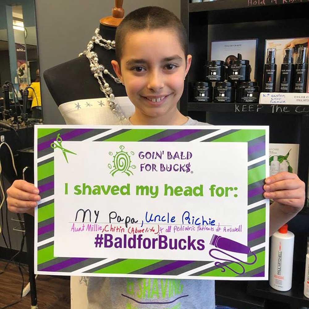 """Child with shaved head holding """"I shaved my head for my papa, Uncle Richie"""" Bald for Bucks sign"""
