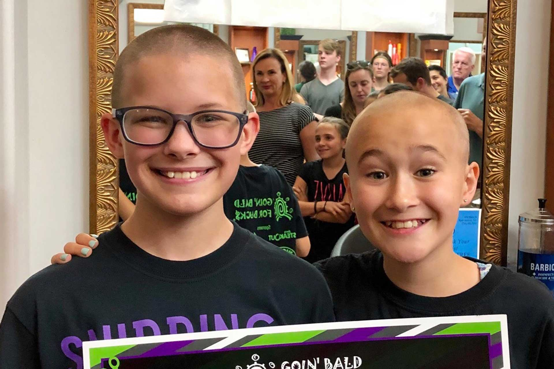 Two children in crowd with shaved heads
