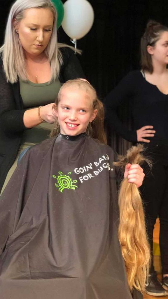 Adult shaving child's head as she holds long hair that was cut off